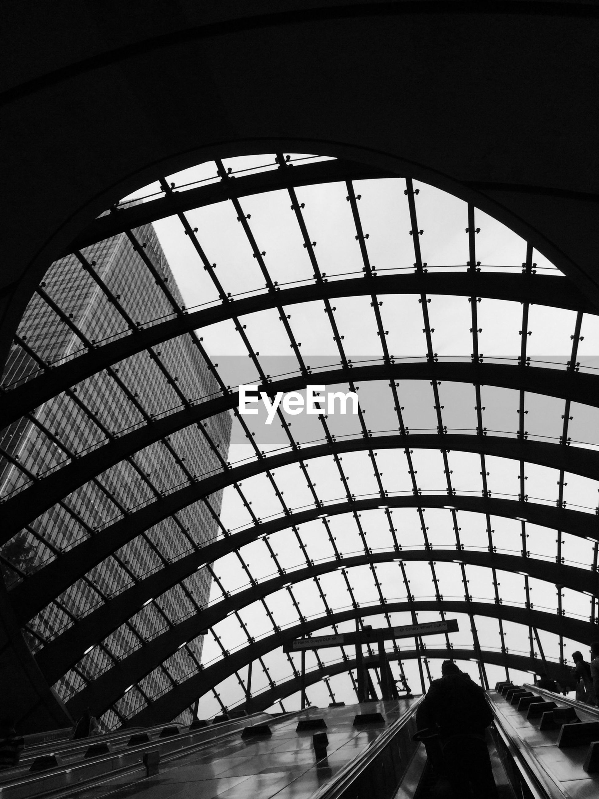 Low angle view of escalator below glass roof