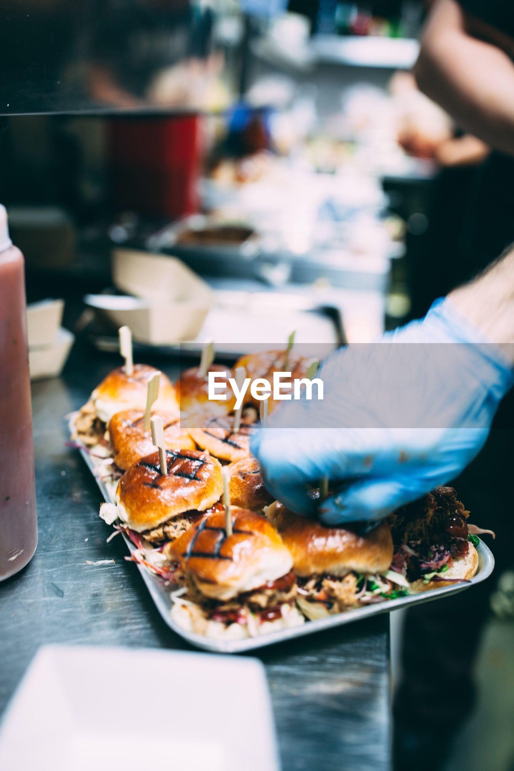 Close-up of man preparing burger on tray at concession stand