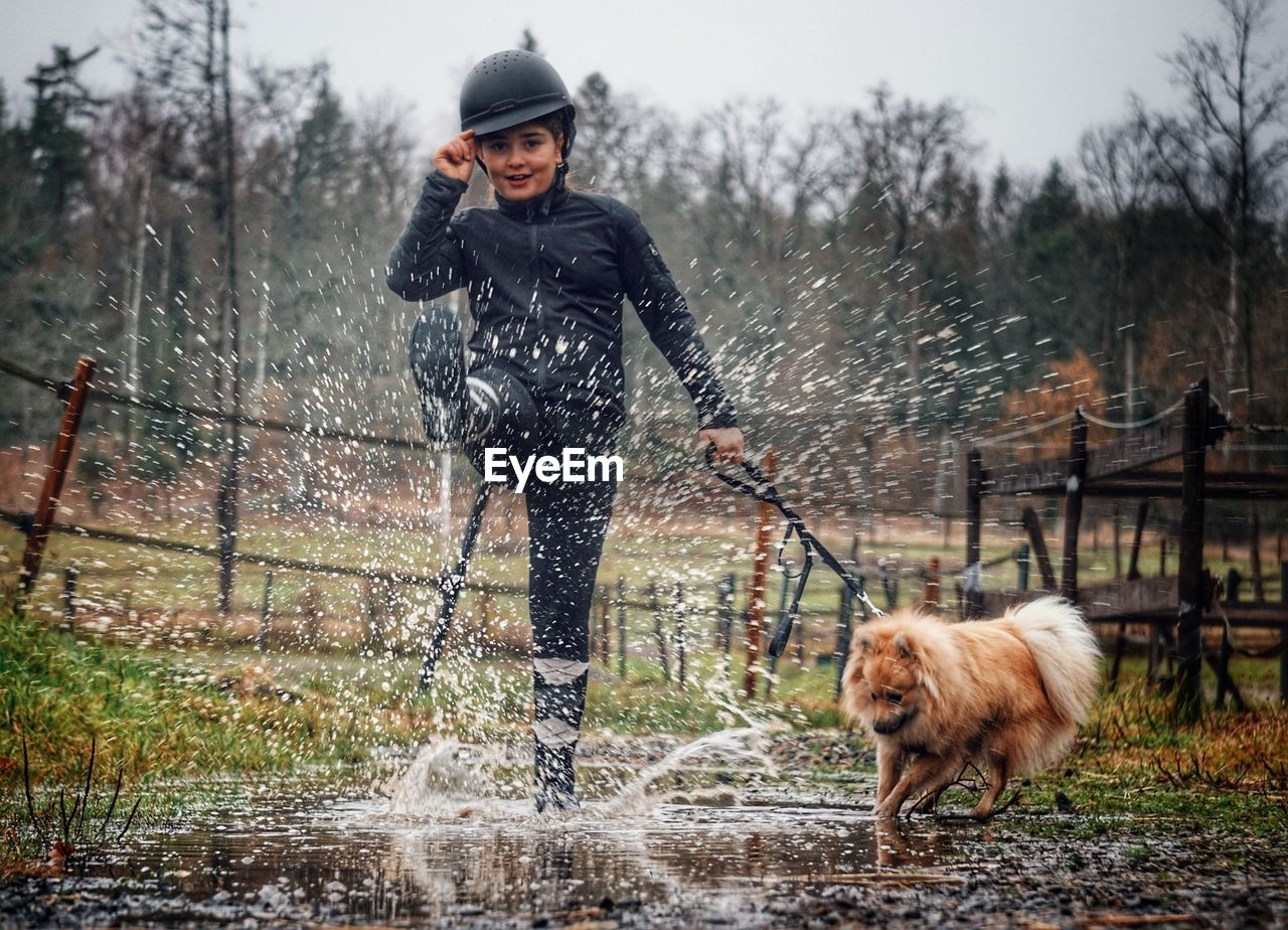 Portrait of girl splashing water while standing by dog