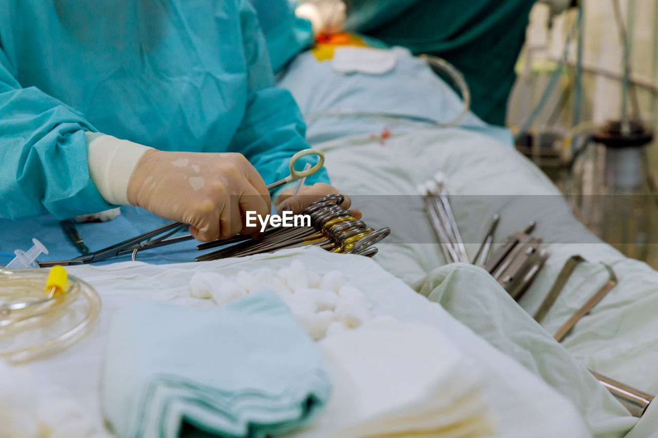 Midsection of doctor holding medical equipment in hospital