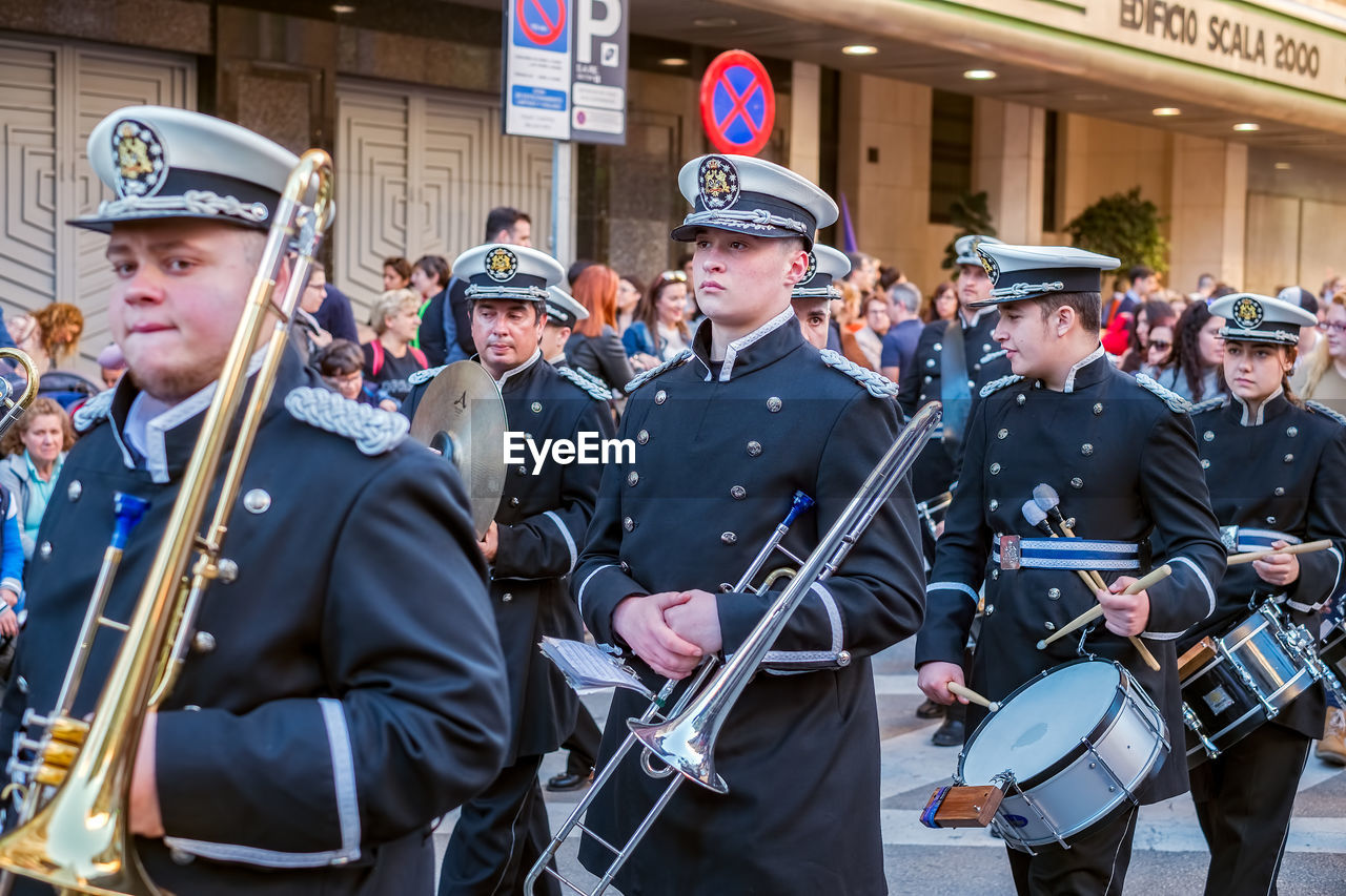 group of people, music, musical instrument, men, real people, uniform, musician, clothing, arts culture and entertainment, day, large group of people, musical equipment, street, artist, crowd, city, marching band, adult, performance, government, outdoors