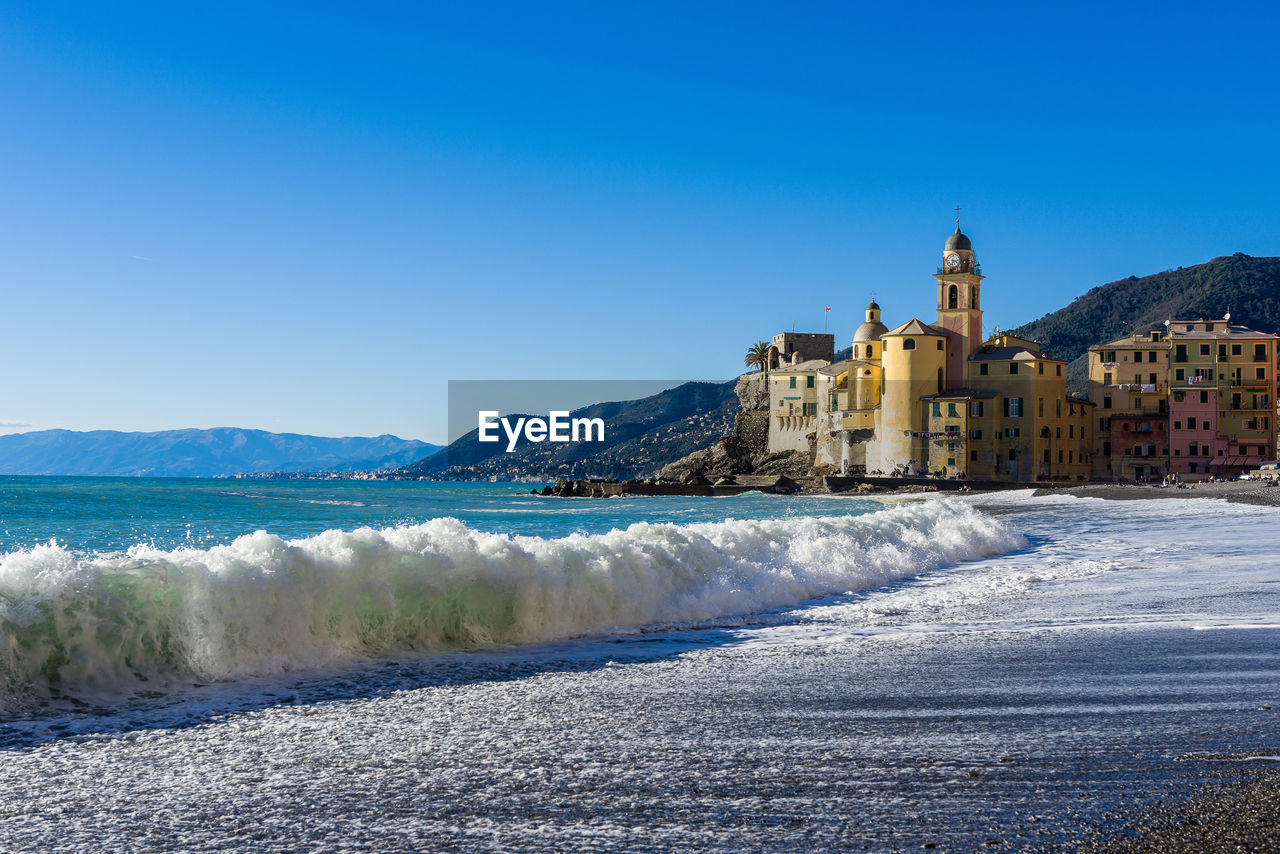 Sea waves rushing towards shore by buildings against clear blue sky