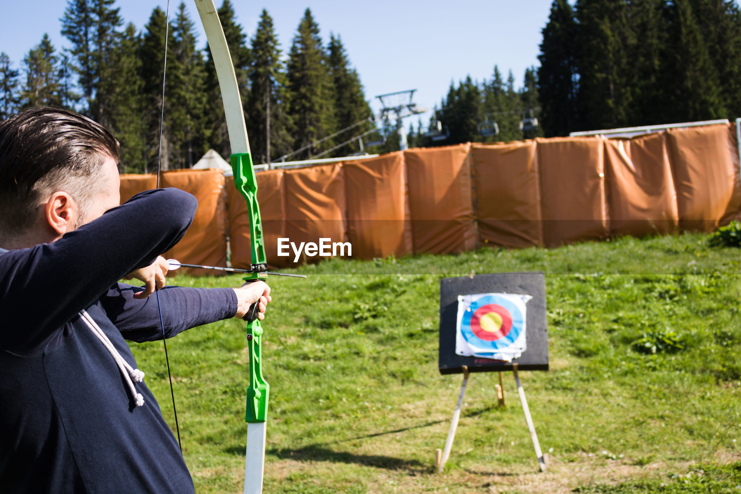 Man using bow and arrow and shooting at the target outdoors.