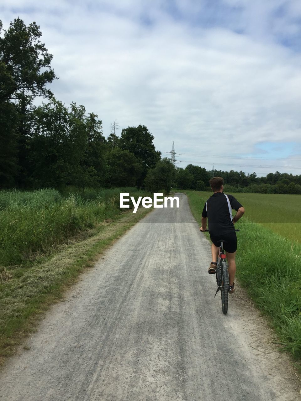 Rear View Of Man Riding Bicycle On Road Against Cloudy Sky