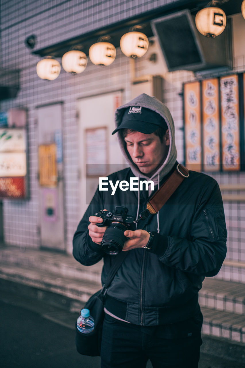 technology, front view, one person, standing, wireless technology, real people, clothing, three quarter length, communication, young men, holding, mobile phone, leisure activity, young adult, lifestyles, smart phone, portable information device, portrait, warm clothing, outdoors