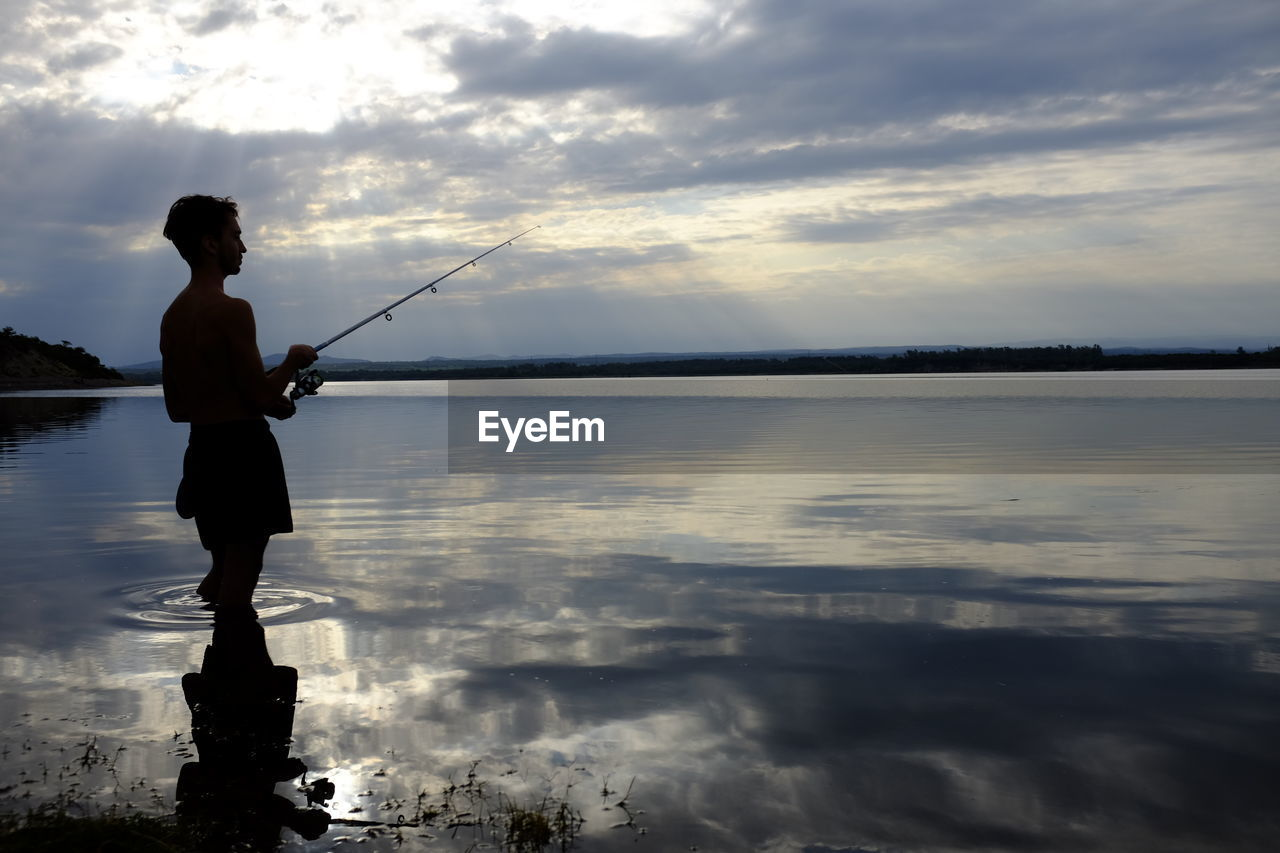 Silhouette Man Fishing In Lake Against Cloudy Sky During Sunset