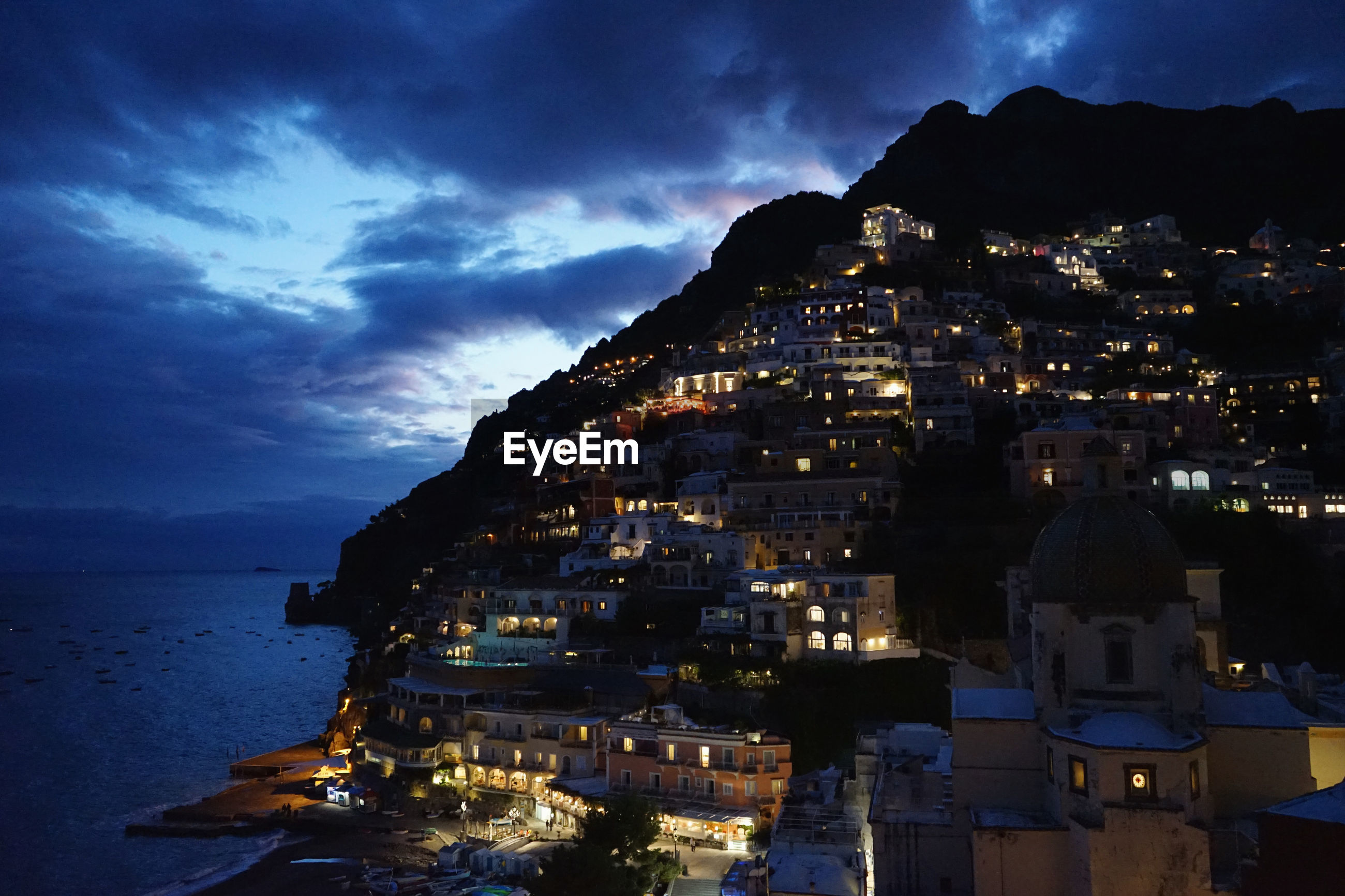 Illuminated houses on mountain by sea against sky at dusk