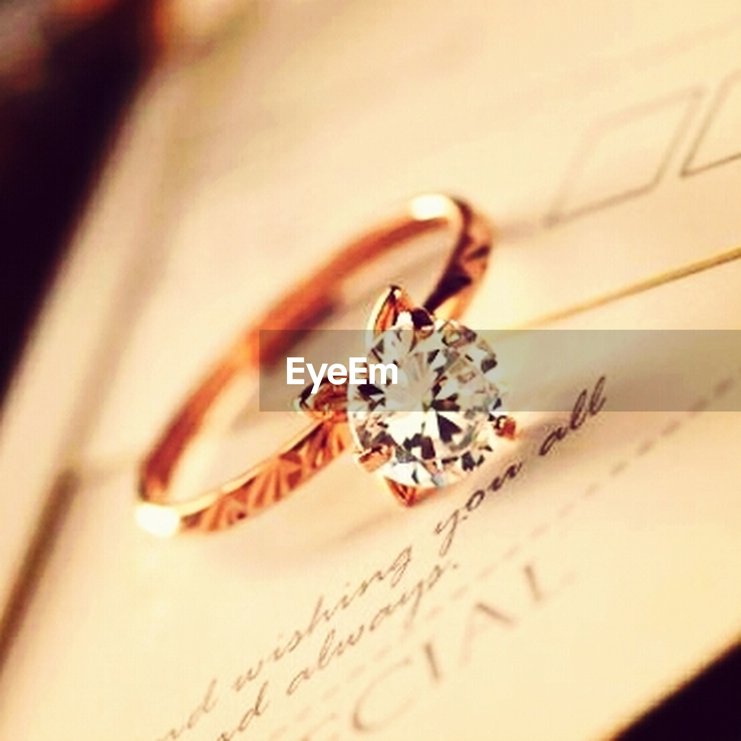 indoors, close-up, table, selective focus, person, focus on foreground, still life, art and craft, high angle view, creativity, text, art, jewelry, part of, paper, flower, decoration, cropped, western script, no people