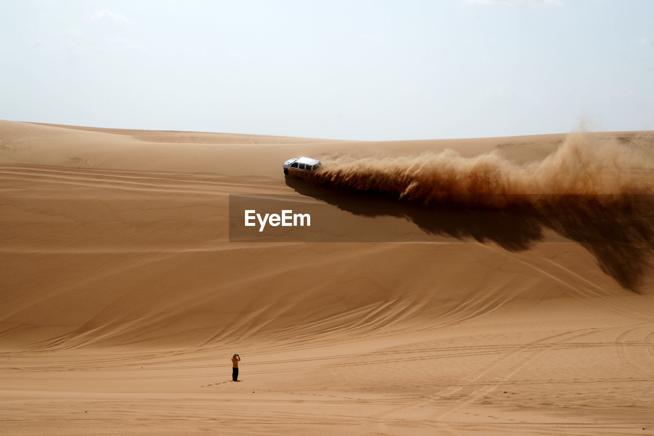 Rear view of man standing near off-road vehicle on desert