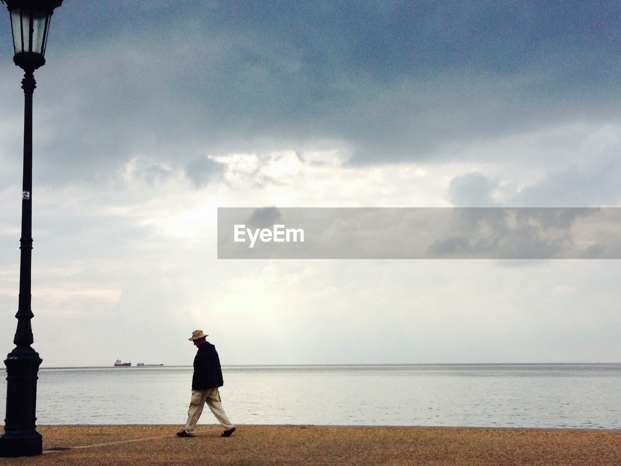 Side-View Of Man Walking On Promenade