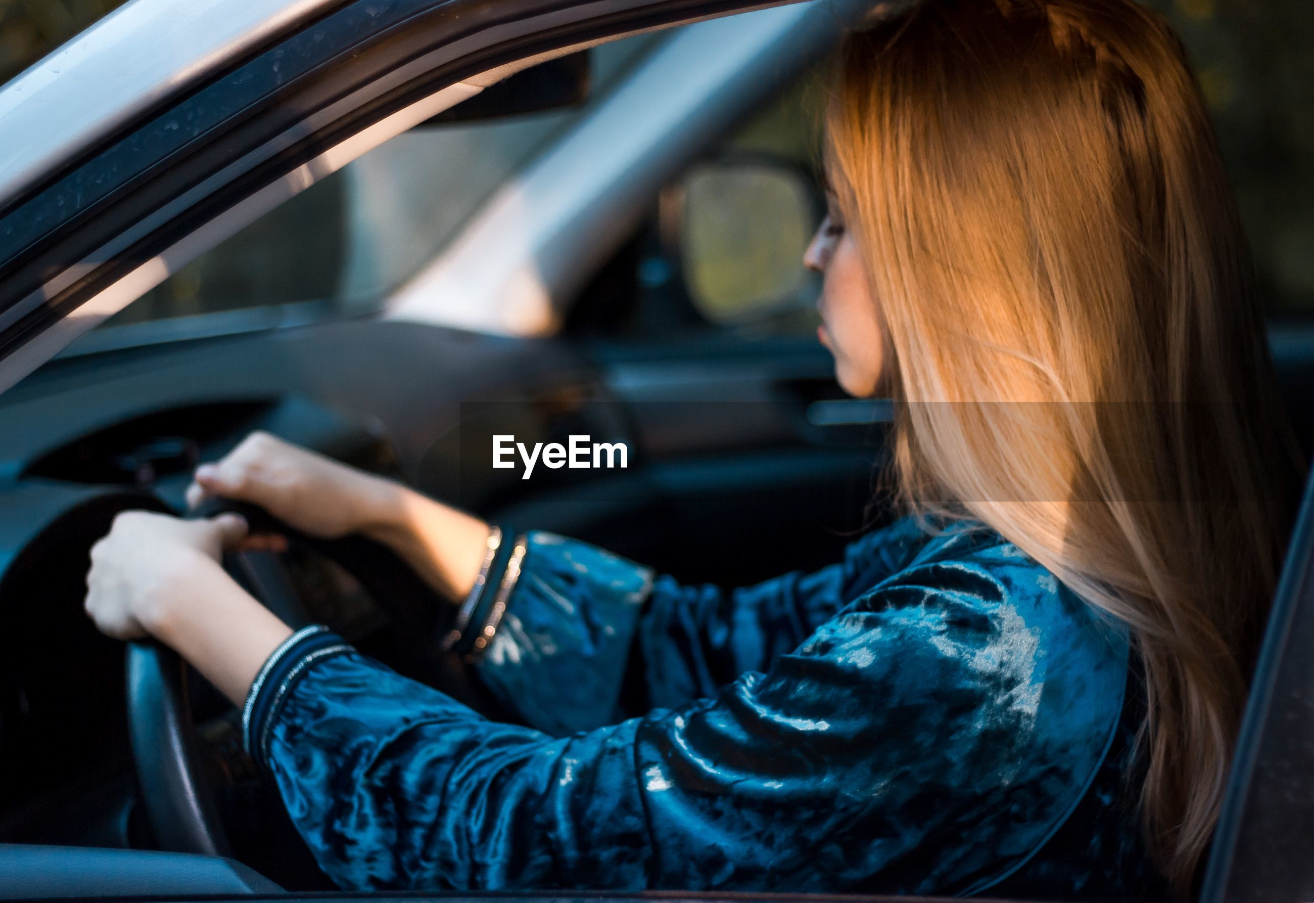 Side view of young woman with blond hair driving car seen through window