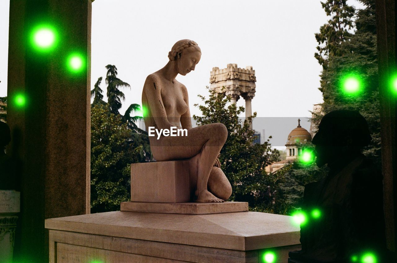 representation, sculpture, human representation, statue, male likeness, art and craft, tree, illuminated, sitting, nature, architecture, plant, creativity, green color, lighting equipment, religion, no people, female likeness, built structure, craft