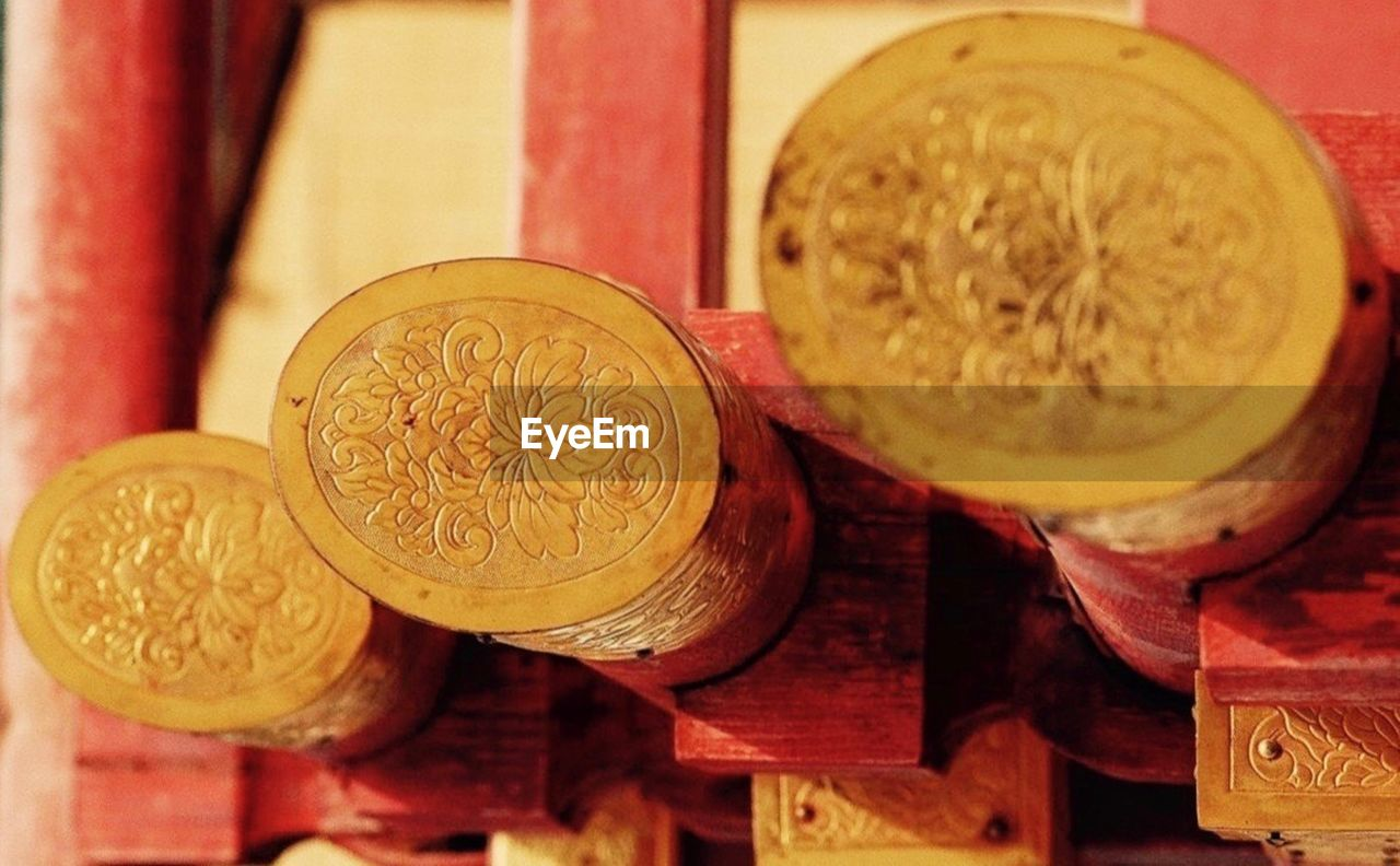 indoors, coin, no people, finance, close-up, still life, currency, business, history, wood - material, focus on foreground, food and drink, circle, geometric shape, the past, high angle view, wealth, art and craft, shape, gold colored, floral pattern, ornate