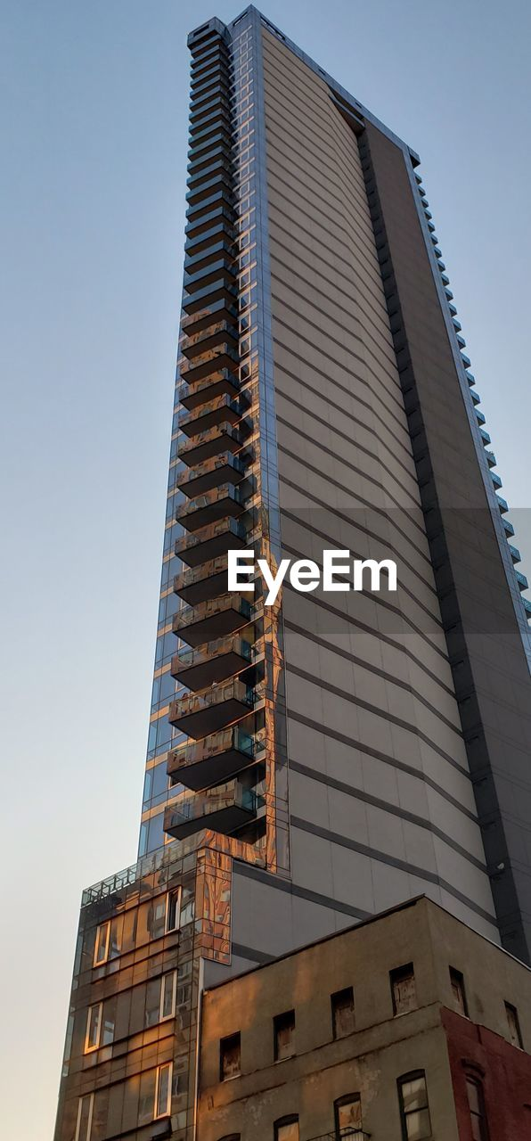 building exterior, built structure, architecture, low angle view, building, sky, city, tall - high, clear sky, office building exterior, day, no people, tower, nature, office, window, skyscraper, modern, outdoors, glass - material, apartment