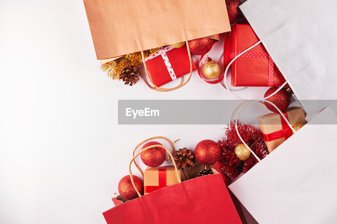 High angle view of shopping bags and gifts against white background