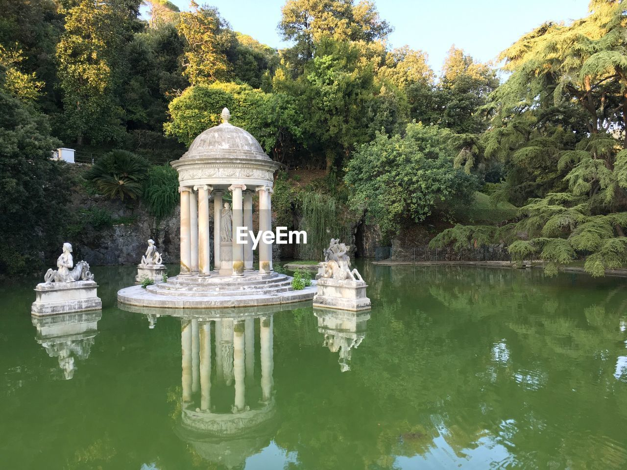 tree, statue, history, architecture, built structure, human representation, travel destinations, day, sculpture, architectural column, outdoors, reflection, water, green color, no people, nature, building exterior, sky, ancient civilization