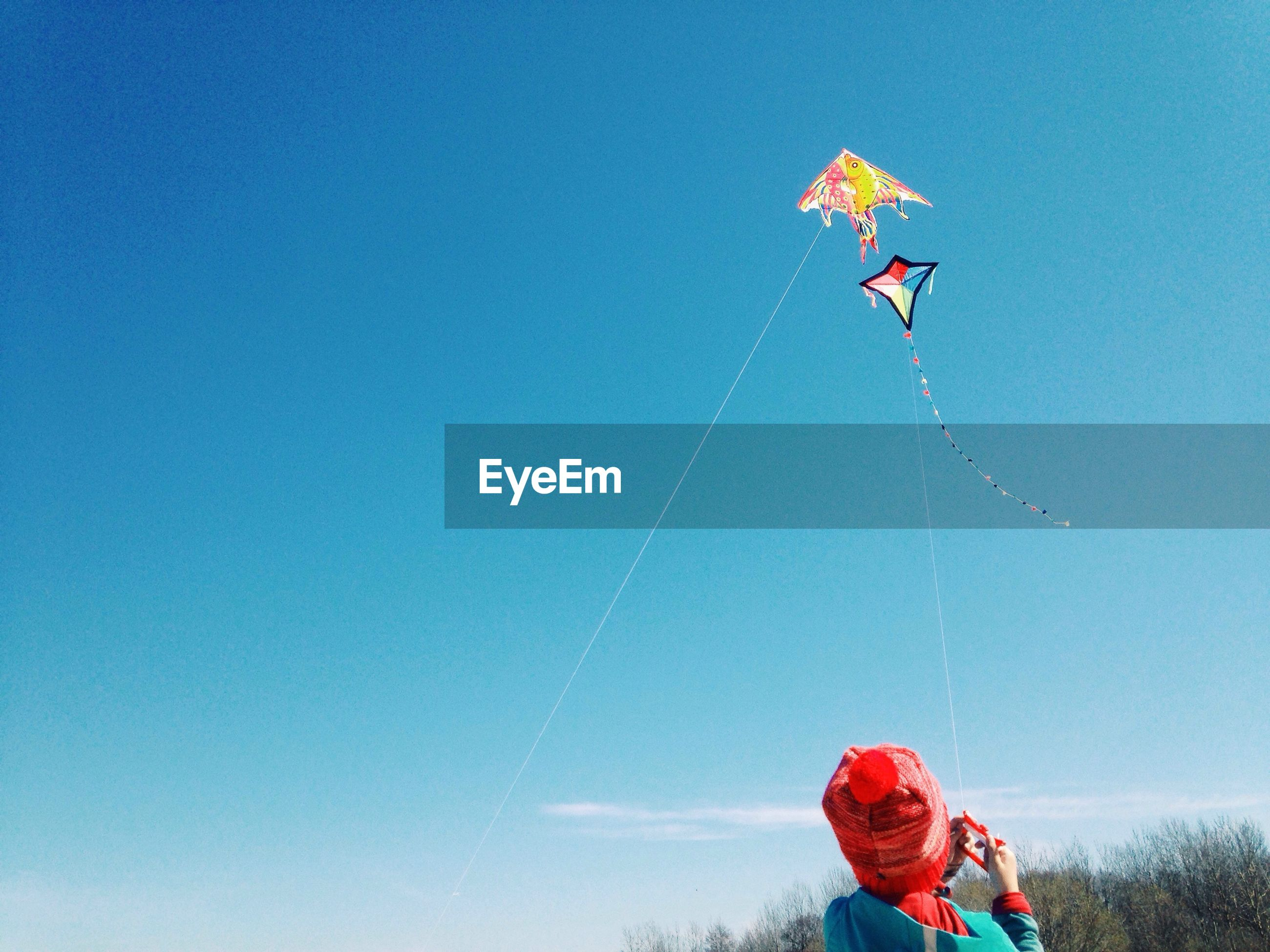 Rear view of person flying kite against clear blue sky