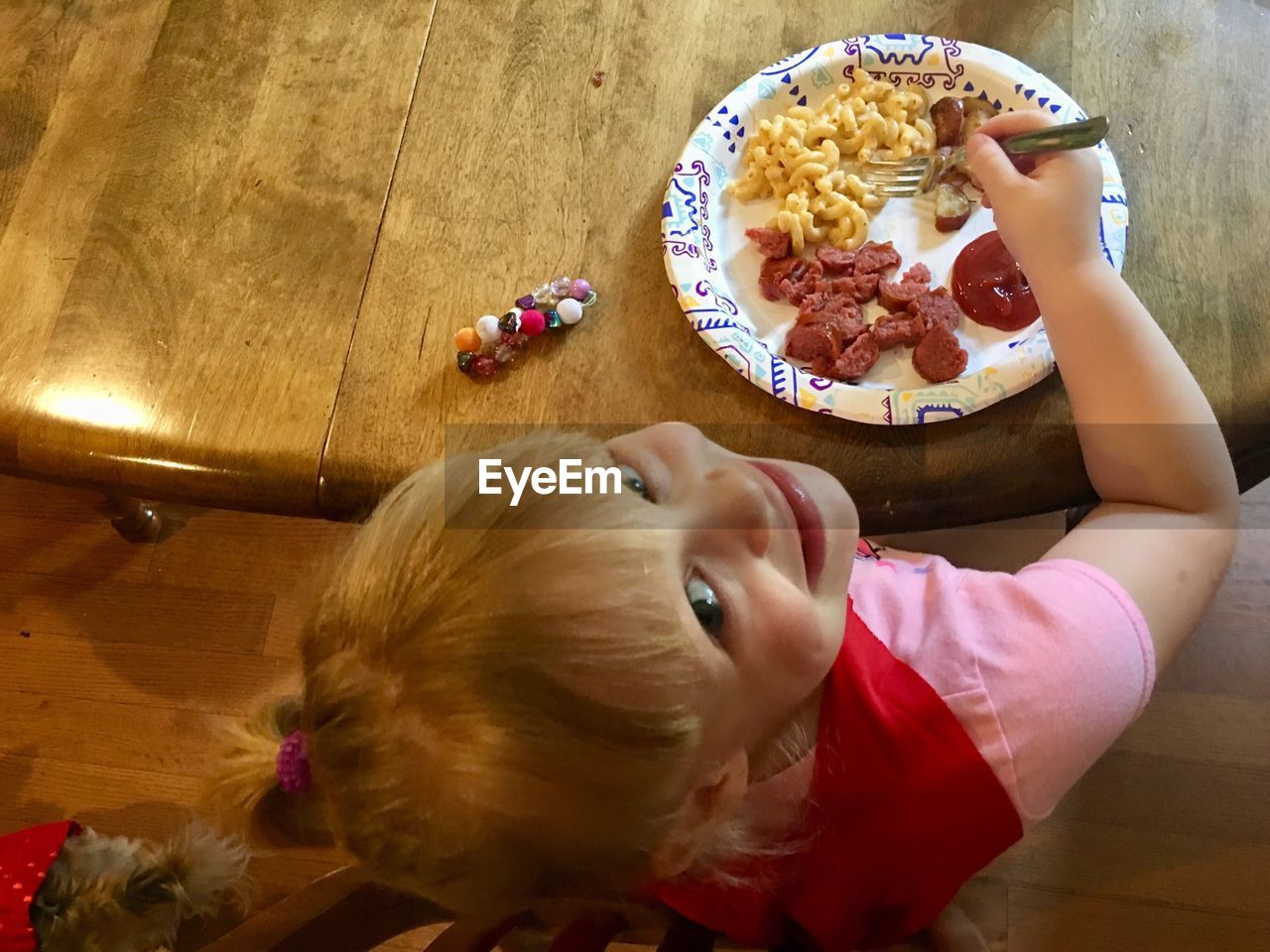 HIGH ANGLE VIEW OF GIRL HAVING BREAKFAST AT HOME