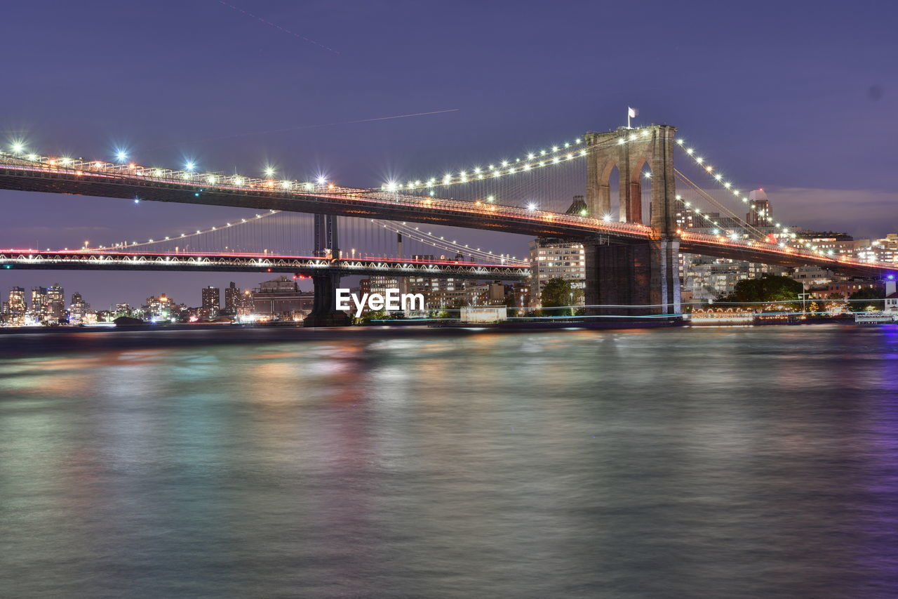 built structure, bridge, architecture, water, bridge - man made structure, connection, illuminated, river, transportation, waterfront, sky, city, night, engineering, nature, suspension bridge, building exterior, reflection, travel destinations, outdoors, cityscape, light, bay