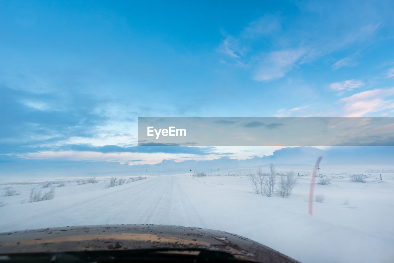 cloud - sky, sky, winter, cold temperature, transportation, snow, no people, mode of transportation, land vehicle, nature, scenics - nature, white color, beauty in nature, travel, day, environment, windshield, road, car, outdoors, car point of view