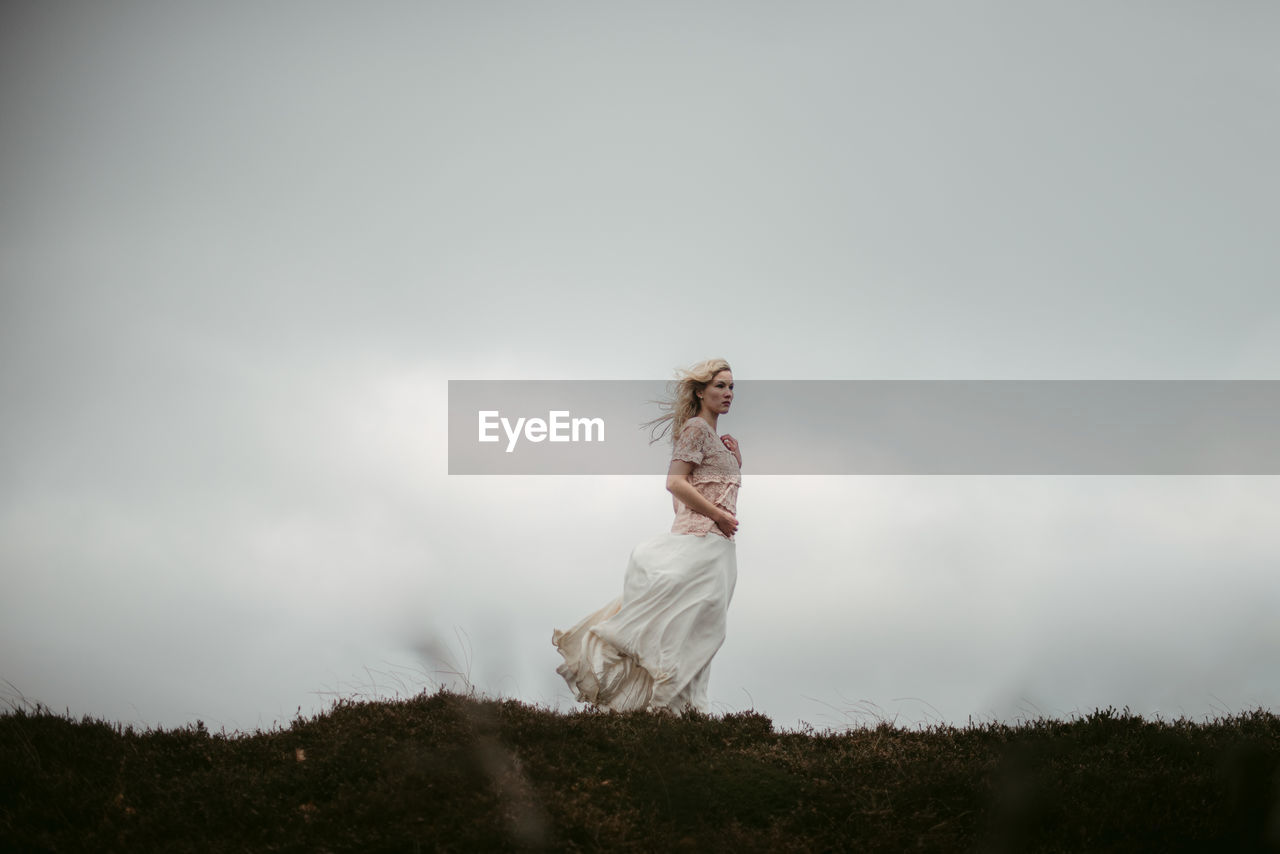 Bride standing on grass against sky