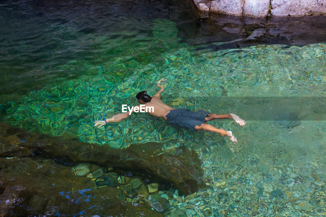 water, swimming, sea, one person, underwater, nature, high angle view, full length, adventure, leisure activity, rock, solid, exploration, trip, vacations, rock - object, holiday, lifestyles, undersea, outdoors, floating on water