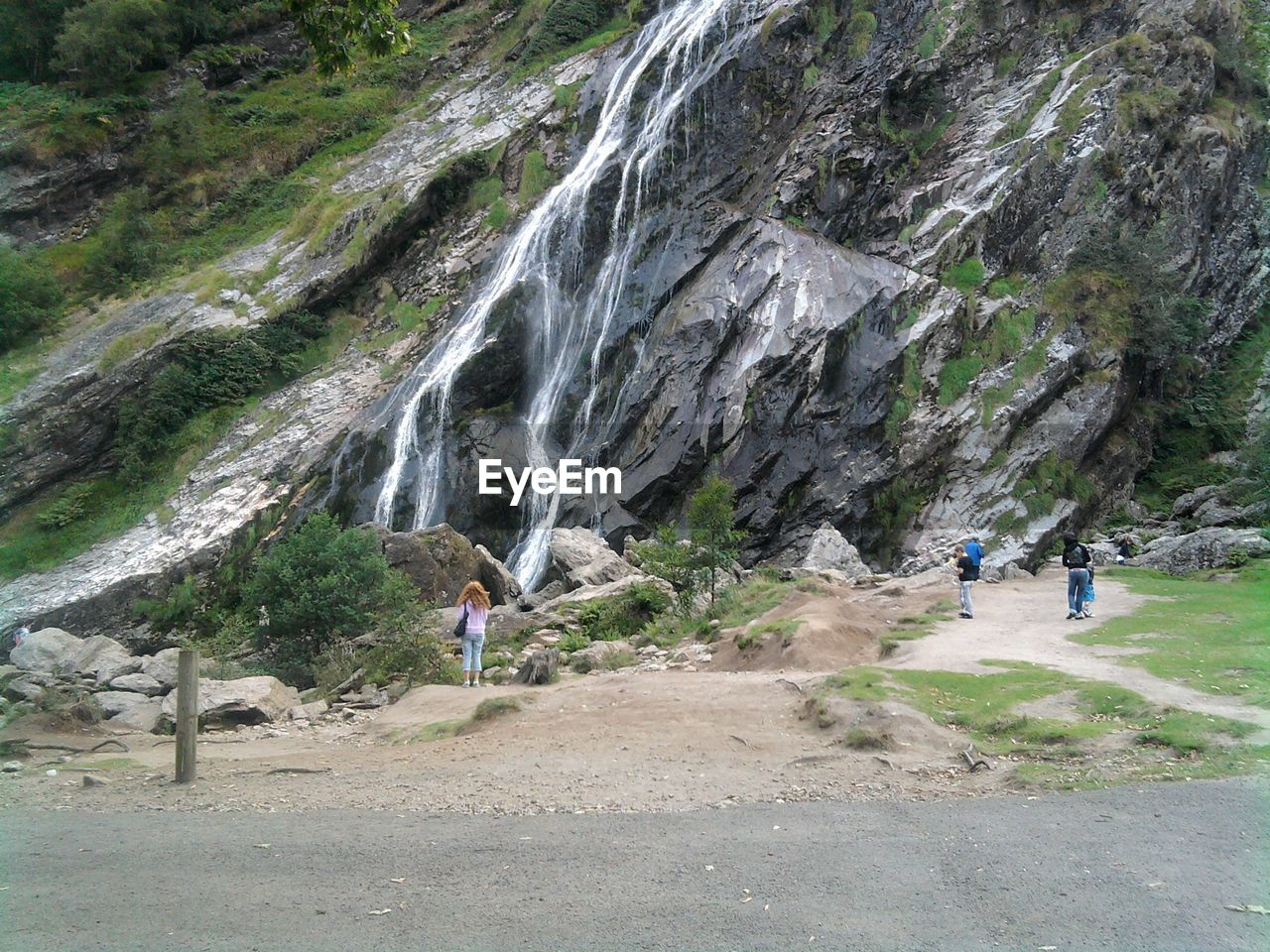 People Standing By Waterfall Against Mountain