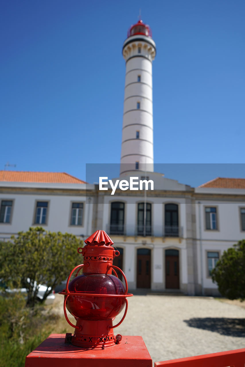 building exterior, built structure, architecture, building, sky, red, clear sky, nature, day, no people, focus on foreground, city, outdoors, sunlight, protection, safety, blue, security, guidance, lighthouse