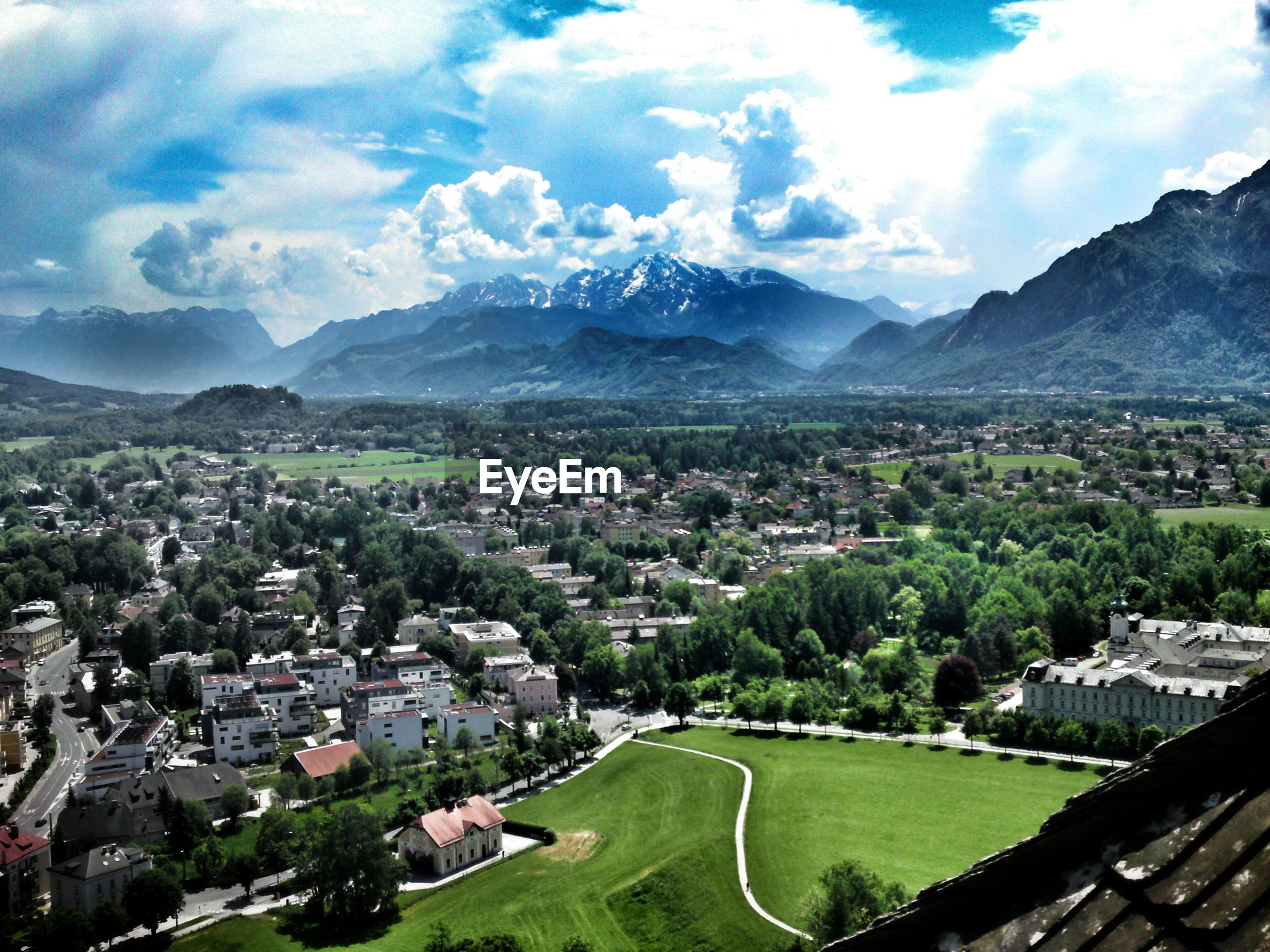 mountain, mountain range, building exterior, day, architecture, sky, outdoors, built structure, landscape, beauty in nature, nature, scenics, tree, no people, cityscape, city, grass