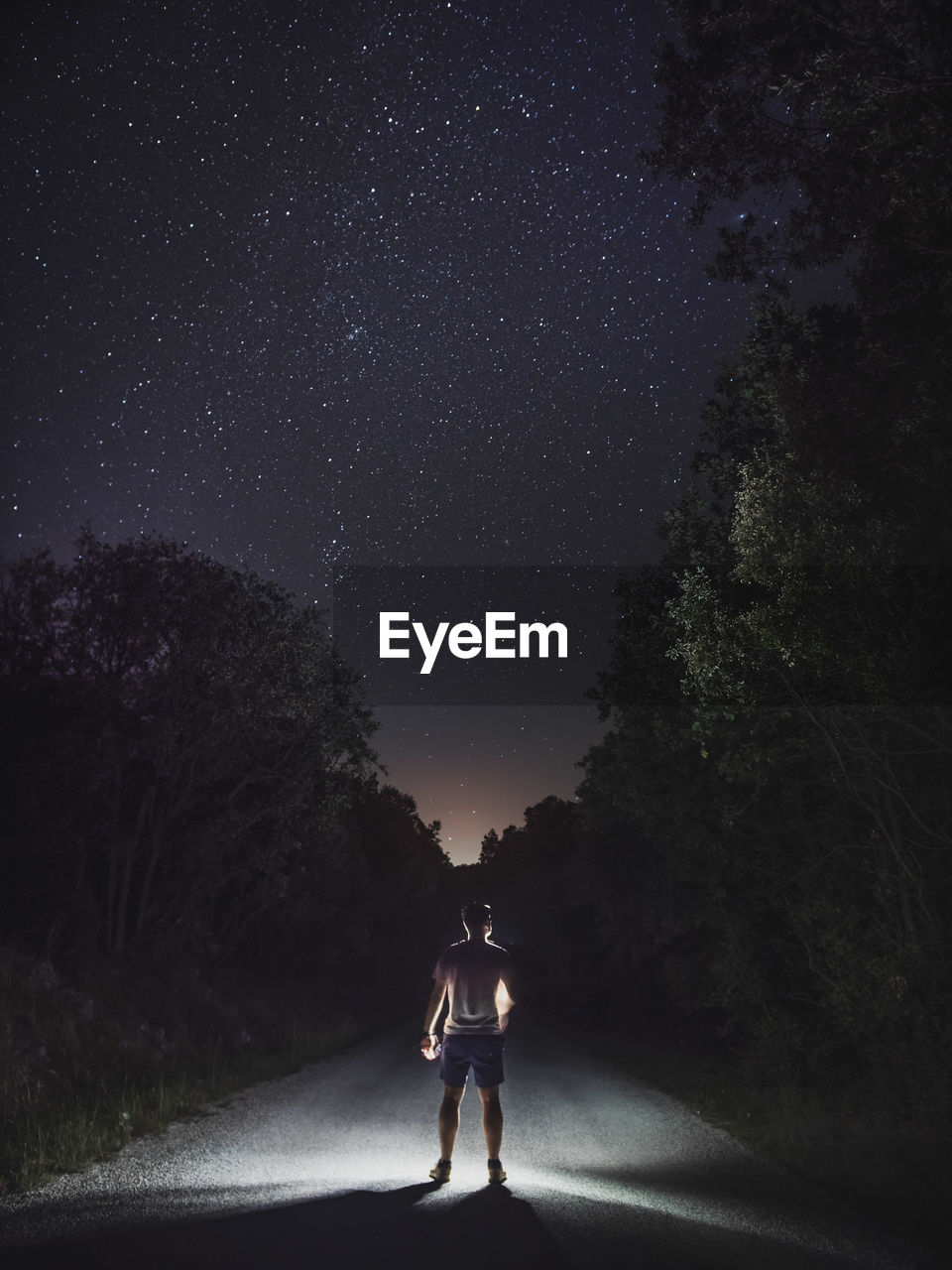 Rear view of man standing on road against sky at night