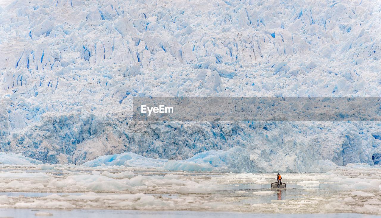 Man in boat on frozen sea