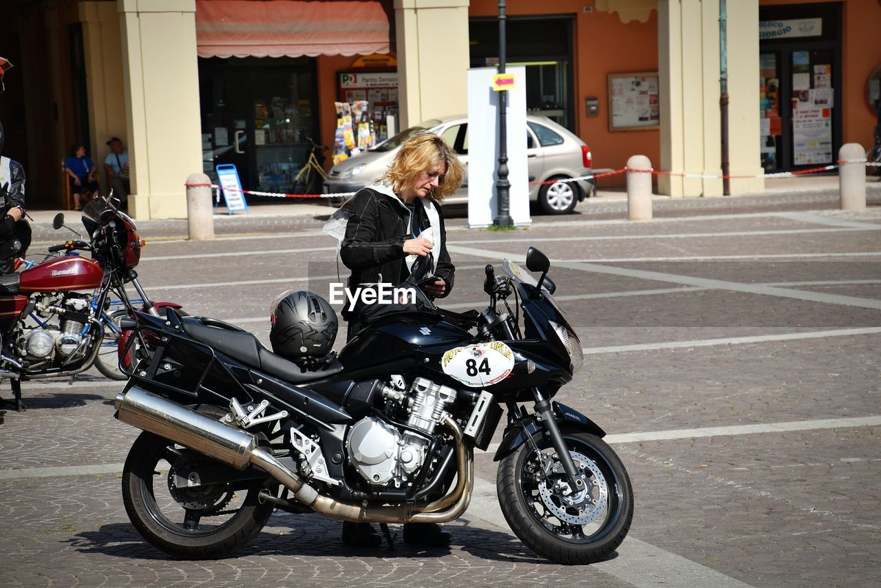 motorcycle, transportation, land vehicle, mode of transport, built structure, biker, building exterior, architecture, street, crash helmet, riding, city life, road, real people, one person, city, adventure, day, outdoors, adult, people