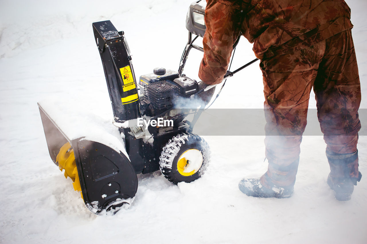 Low Section Of Man Cleaning Snow With Machinery