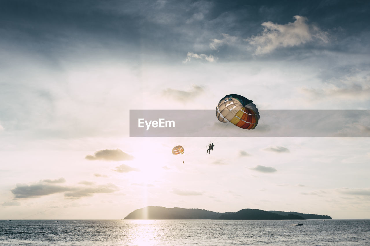 People paragliding over sea against sky