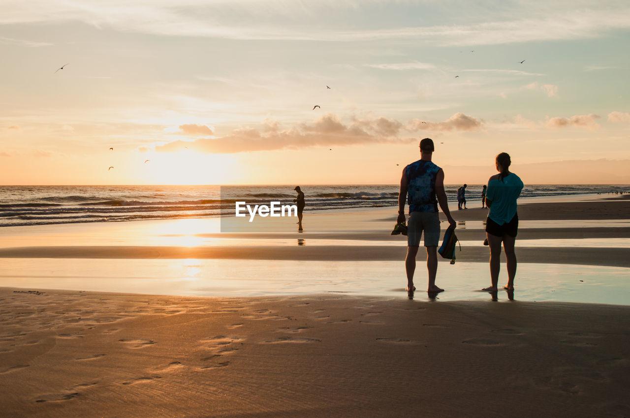 REAR VIEW OF SILHOUETTE MEN WALKING ON BEACH AGAINST SKY