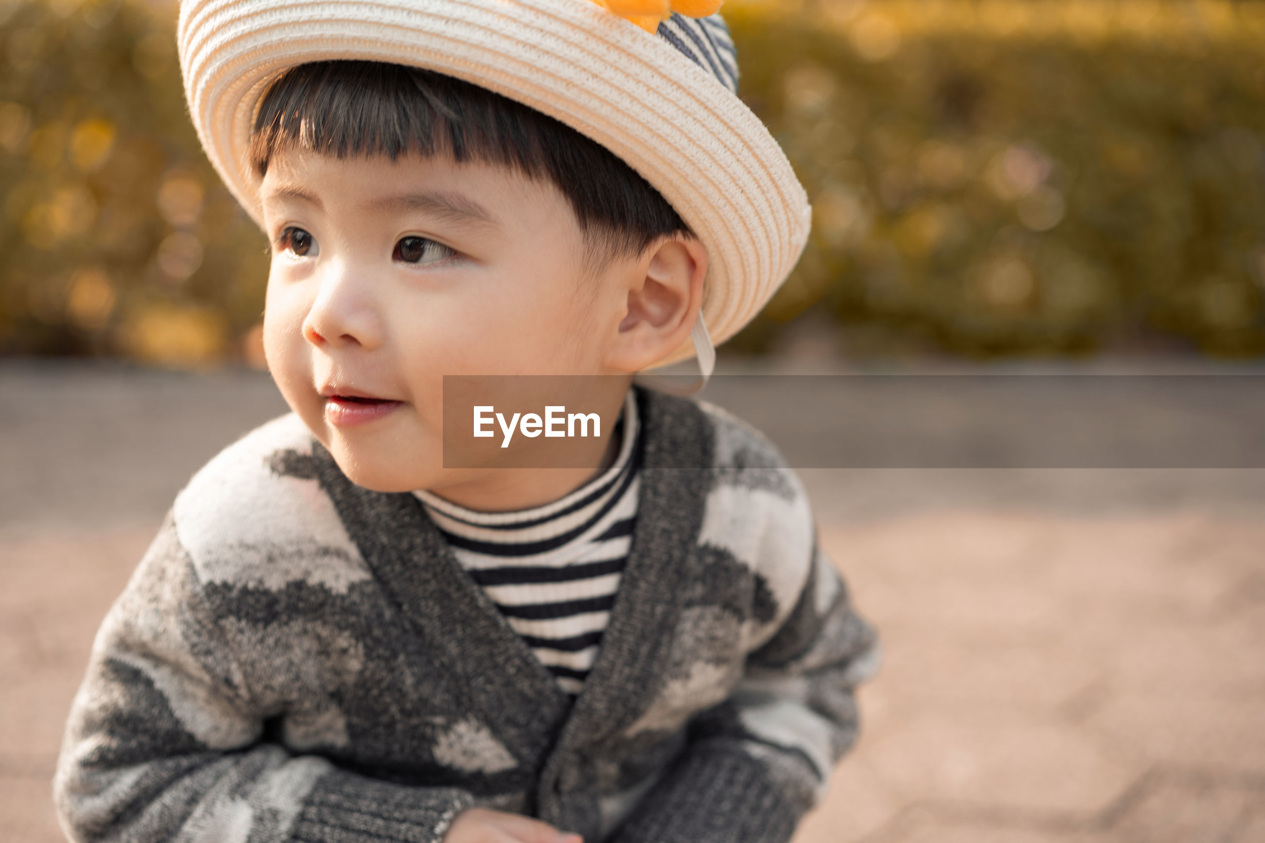 Close-up of cute baby boy looking away while standing outdoors