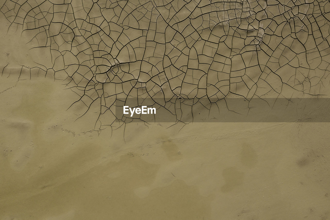 High Angle View Of Sand By Cracked Field