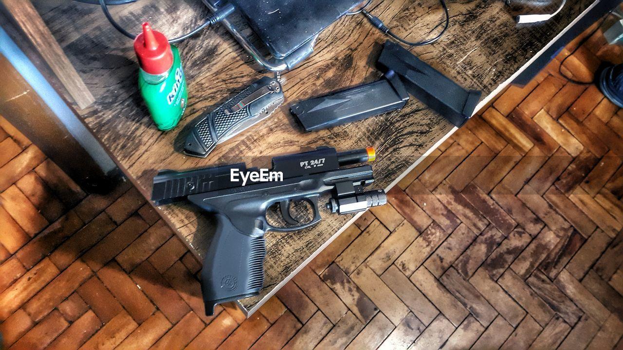 high angle view, wood - material, weapon, table, hardwood floor, indoors, no people, handgun, day