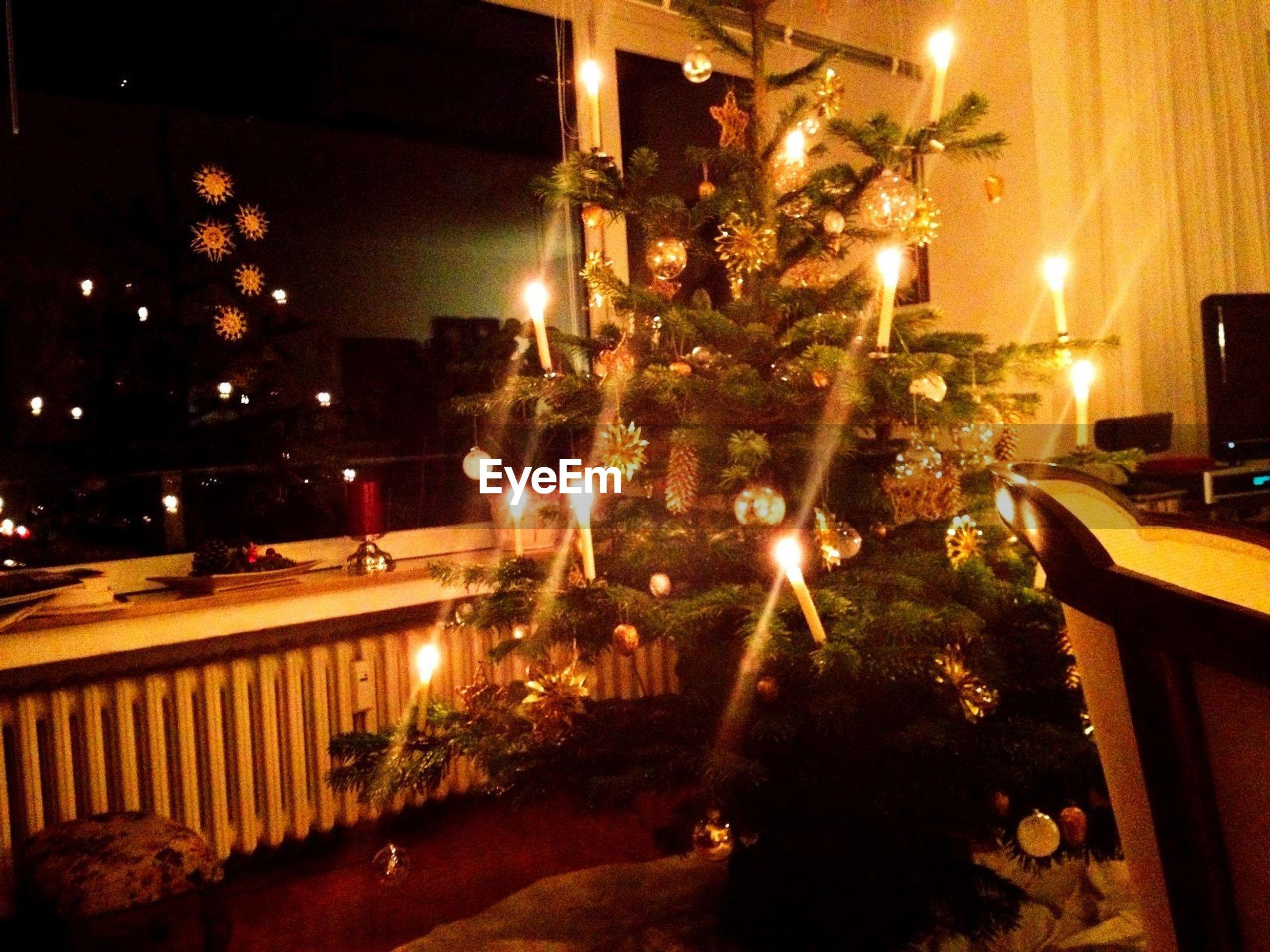 Illuminated christmas tree by window at home