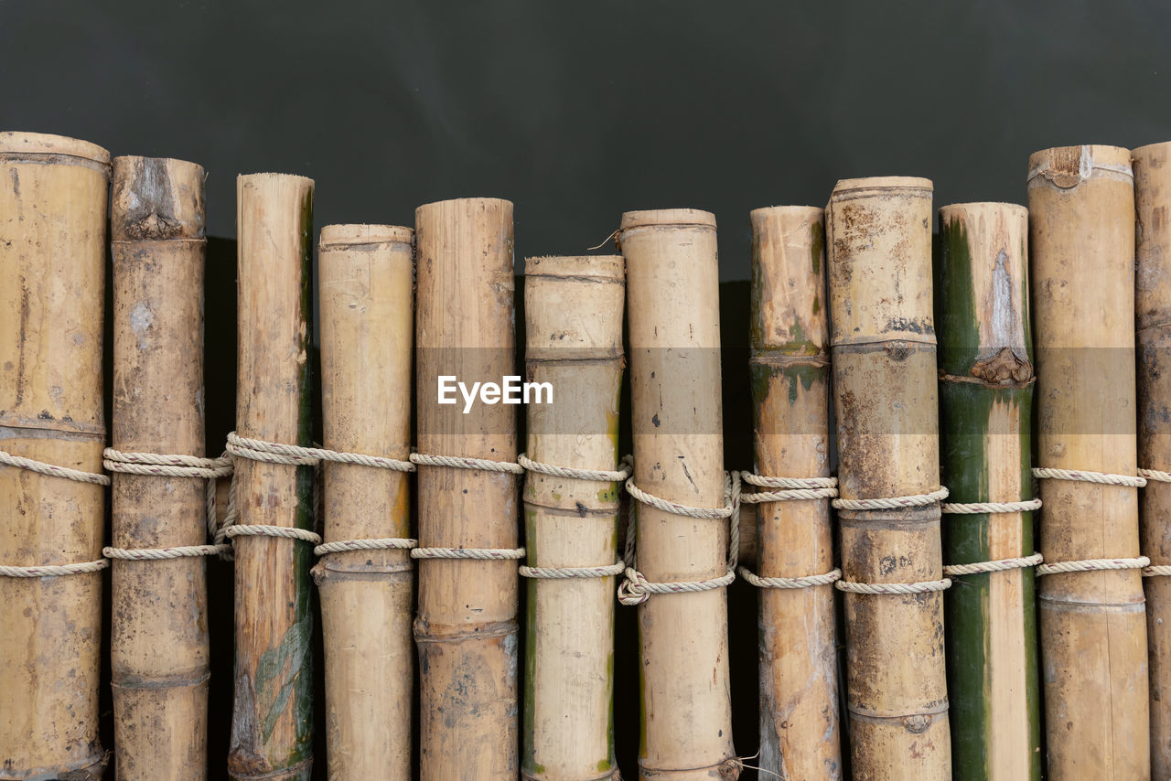 wood - material, bamboo - material, no people, bamboo, side by side, close-up, bamboo - plant, large group of objects, focus on foreground, day, stack, in a row, nature, brown, outdoors, pattern, still life, sunlight, group, backgrounds