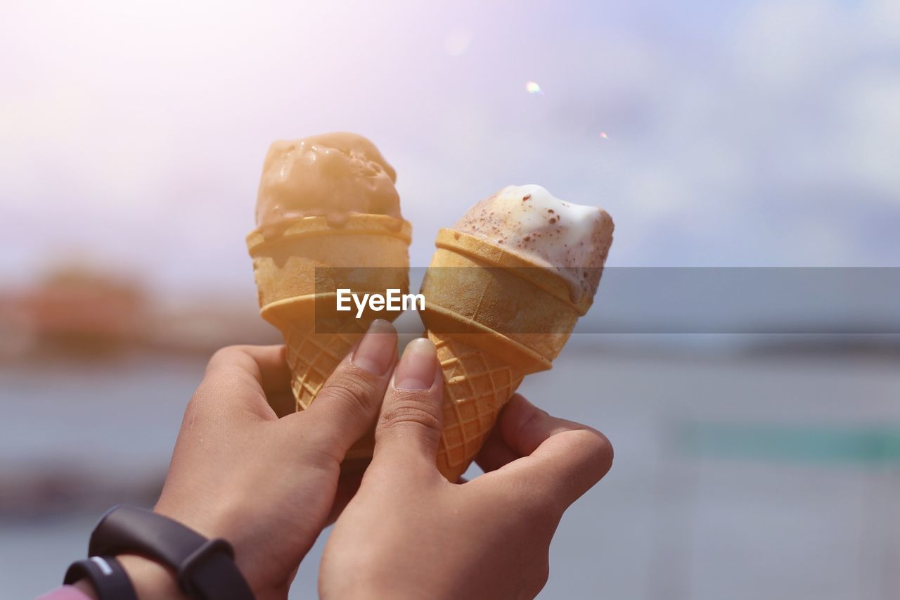 human hand, holding, food and drink, hand, sweet food, focus on foreground, ice cream, food, sweet, frozen food, dairy product, real people, frozen, human body part, dessert, one person, indulgence, lifestyles, temptation, unhealthy eating, outdoors, finger, frozen sweet food, melting