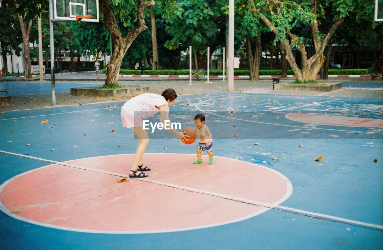 Mother and son playing basketball on court