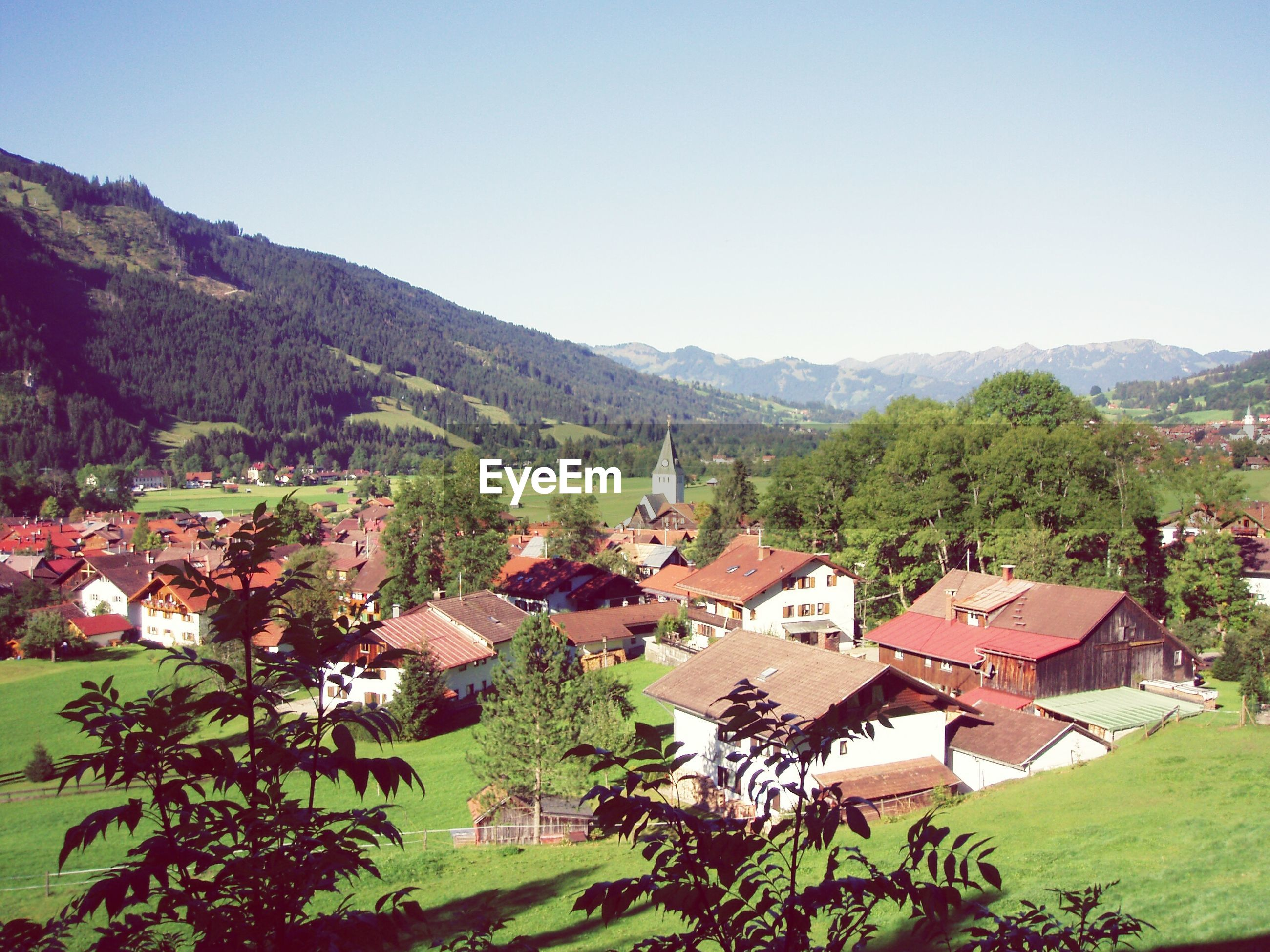 mountain, building exterior, architecture, built structure, clear sky, house, tree, mountain range, high angle view, residential structure, landscape, town, copy space, hill, village, residential building, residential district, green color, townscape, nature