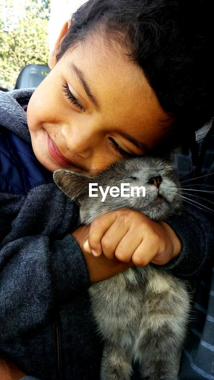 Close-up of young boy hugging cat