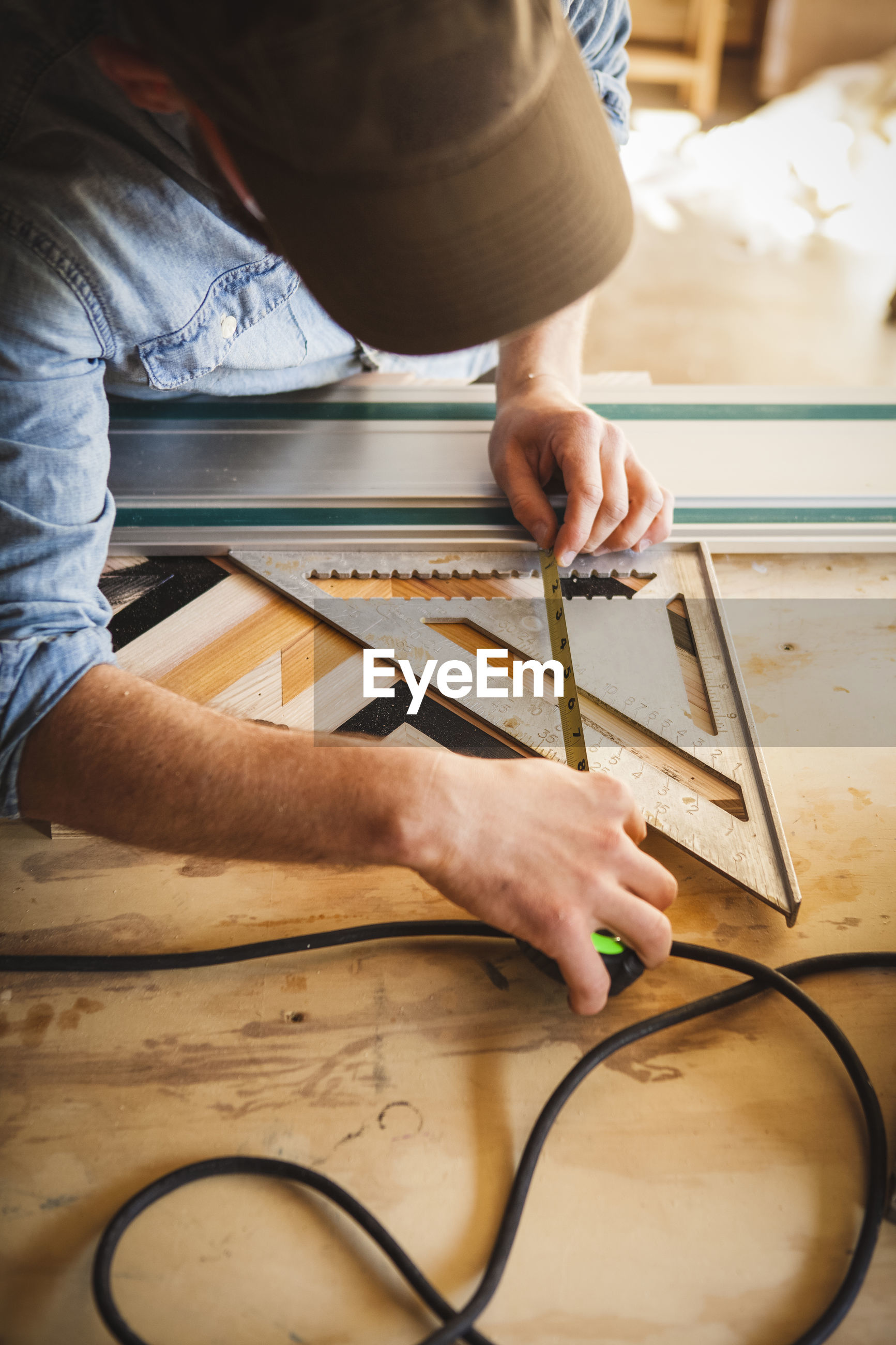 MIDSECTION OF MAN WORKING ON WOODEN TABLE