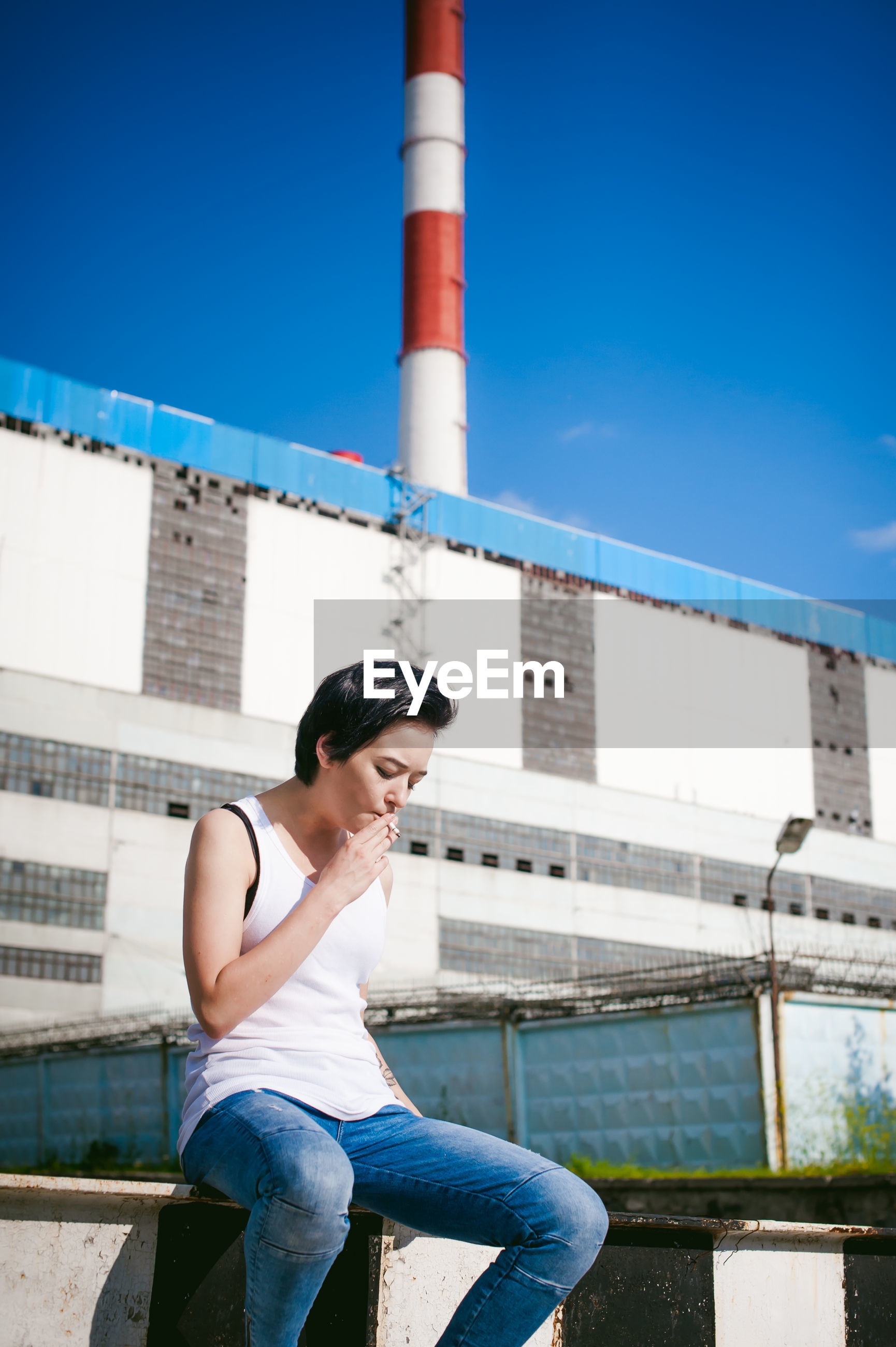 Young woman smoking cigarette while sitting on barricade against factory