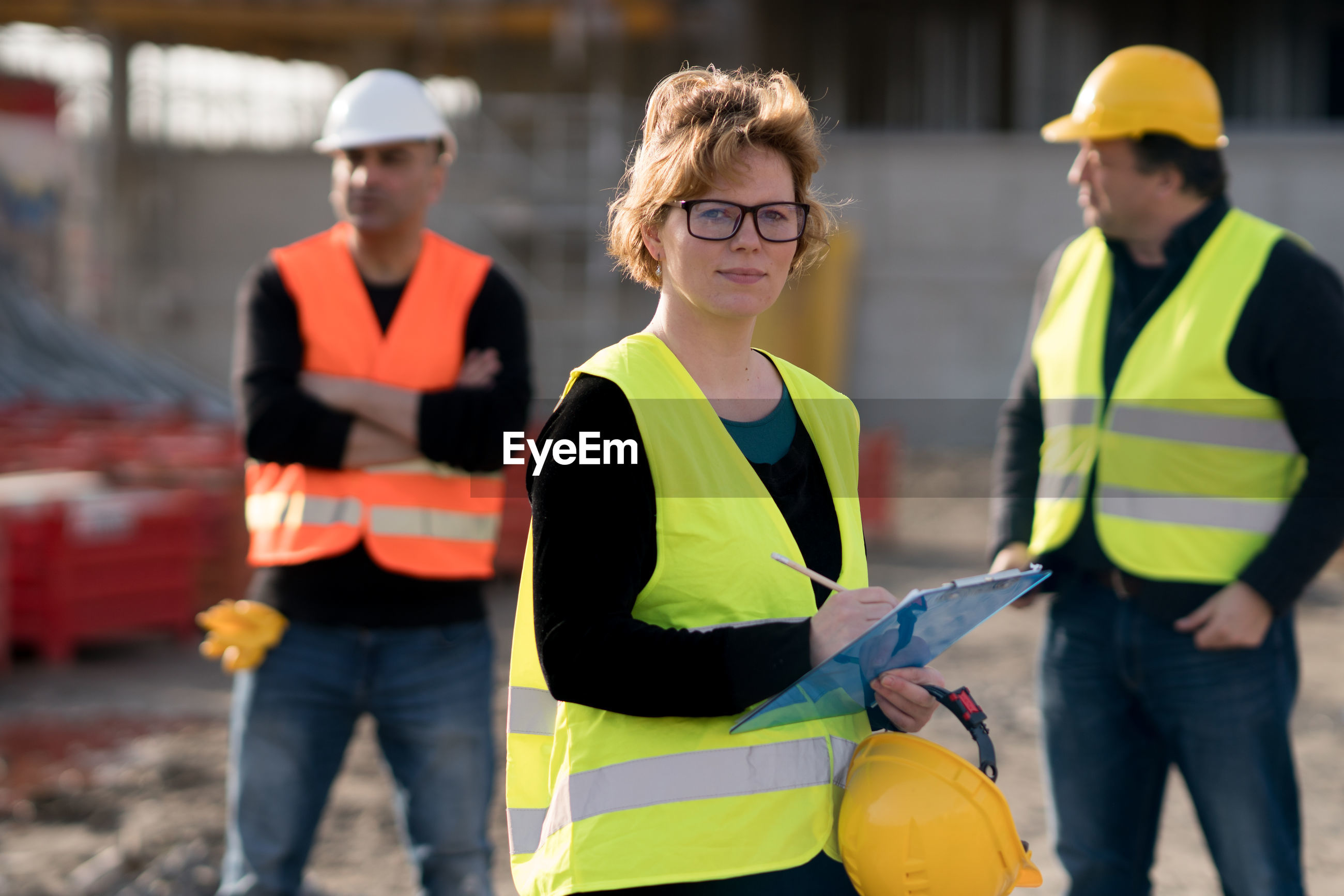 Portrait of engineer standing with clipboard at construction site