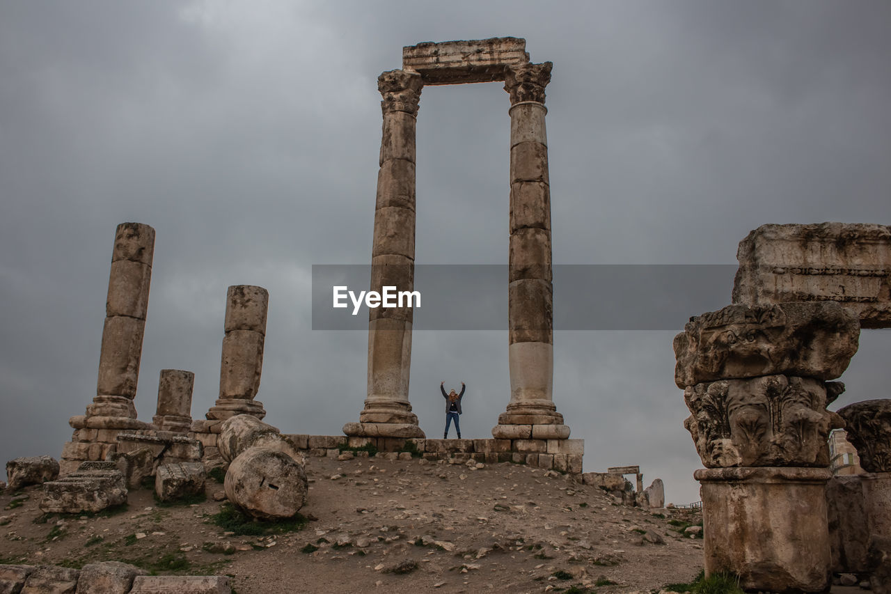 Woman with arms raised standing at temple of hercules
