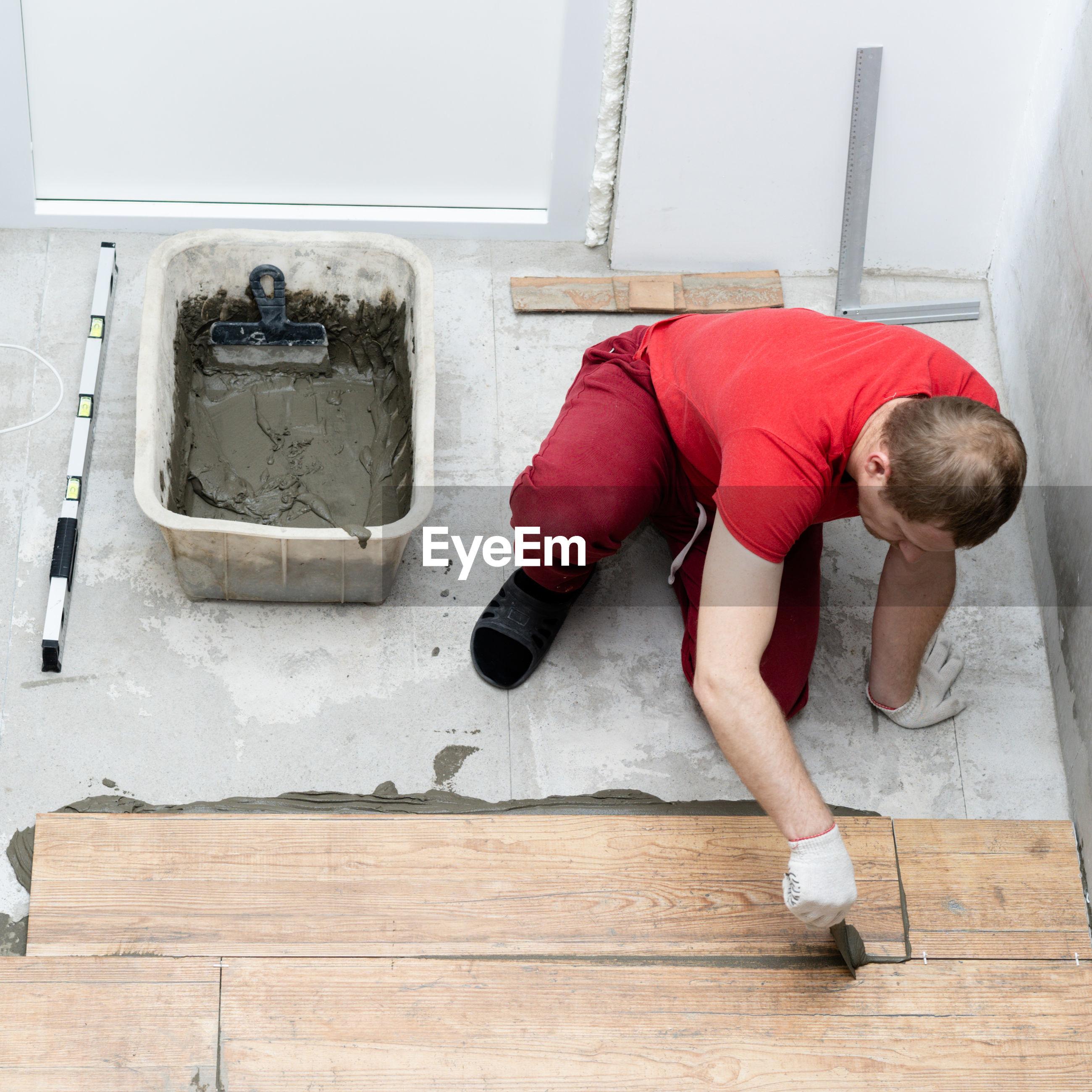 Man installing hardwood floor at home