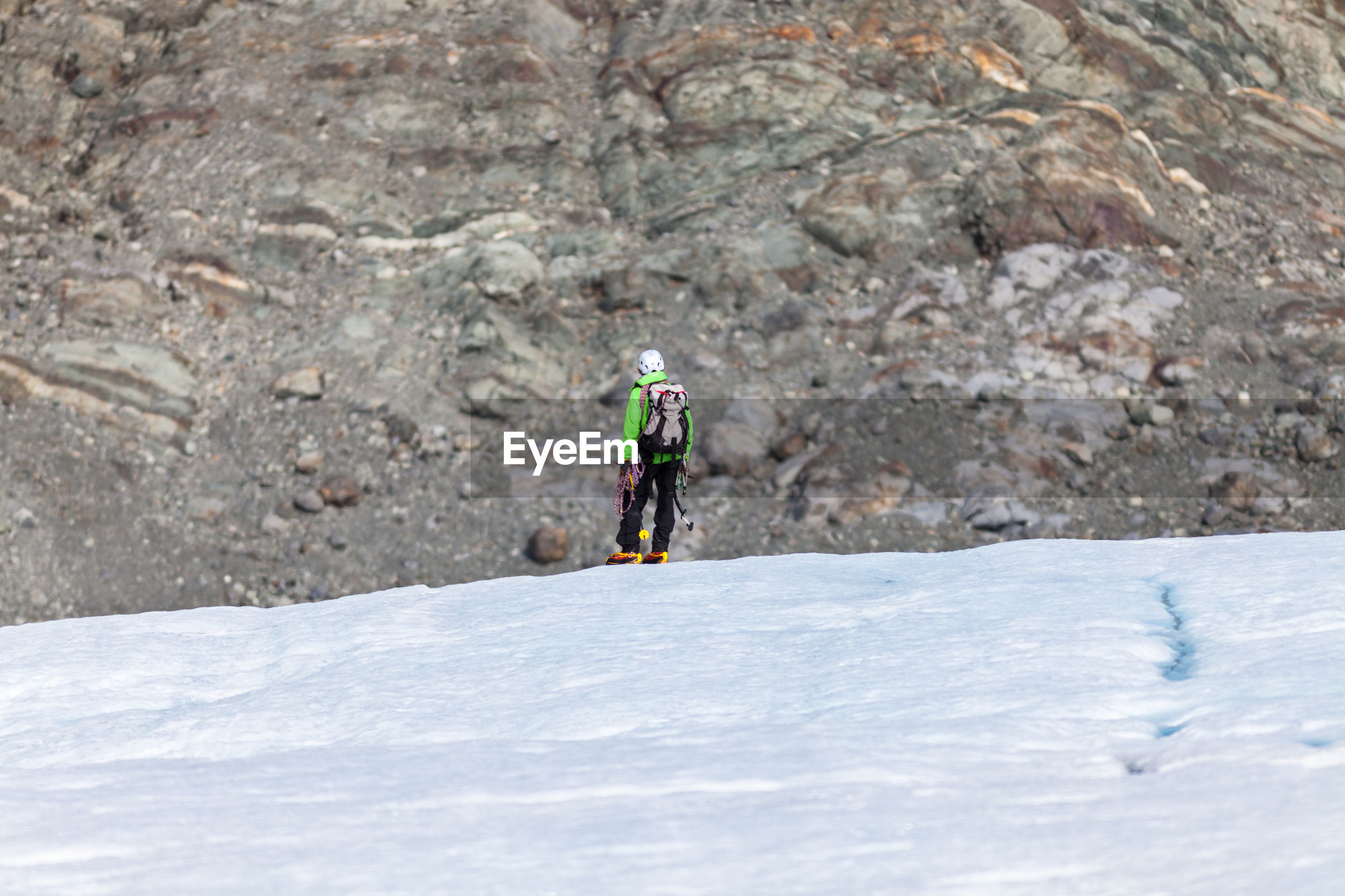 REAR VIEW OF PERSON ON ROCK